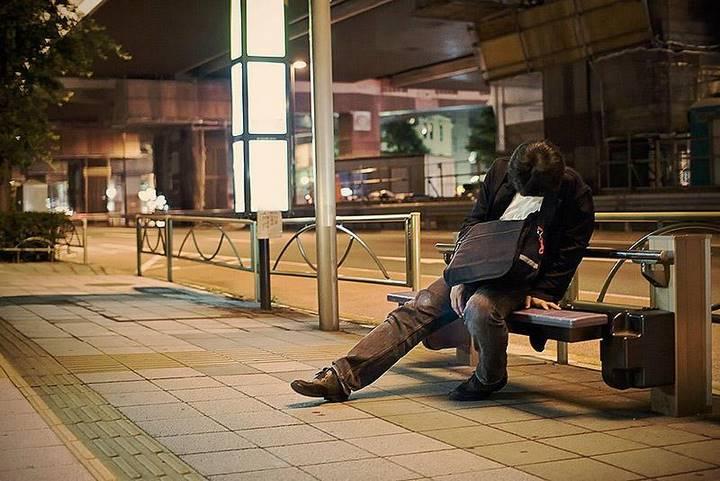 Изнуренные работой жители Токио, спящие на улице