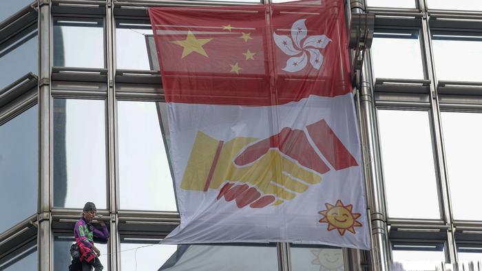 Не все остались довольны трюком: французский «Человек-паук» поднимает на башню Гонконга «Знамя мира»