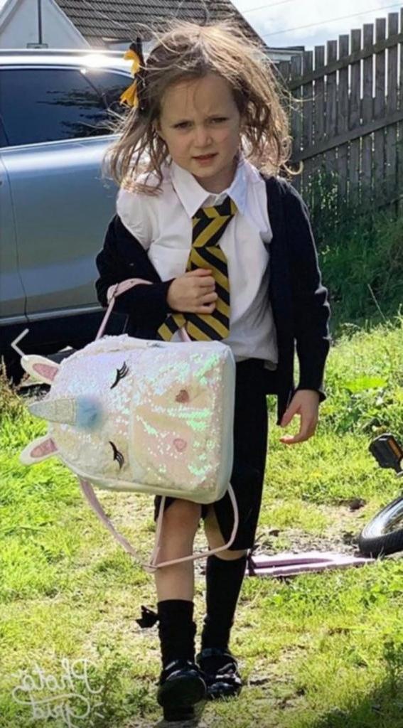 Веселая фотография показывает, что первый день в школе сказался на маленькой девочке