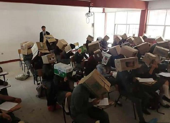 Учитель на экзамене надевает своим ученикам коробки на головы, чтобы они не списывали
