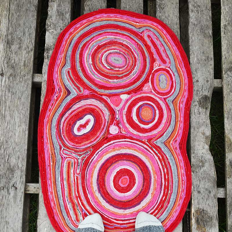 Подруга сделала своими руками яркий коврик из старых свитеров: смотрится очень стильно