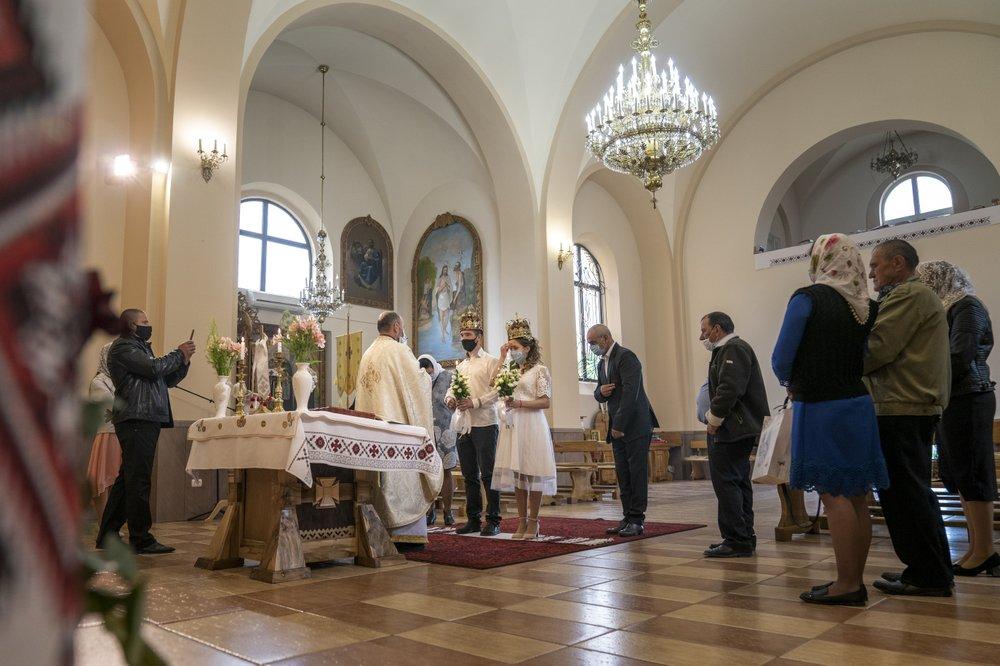 В масках, перчатках, а порой и в защитных комбинезонах: украинские священники вернулись к своим обязанностям